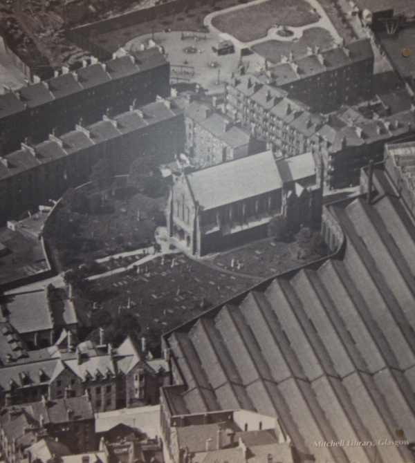 Old photo displayed on an exhibition panel, showing the church flanked by shipbuilding warehouses in 1900