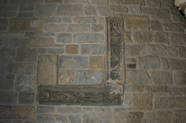 Old carvings incorporated in walled-up nave arch